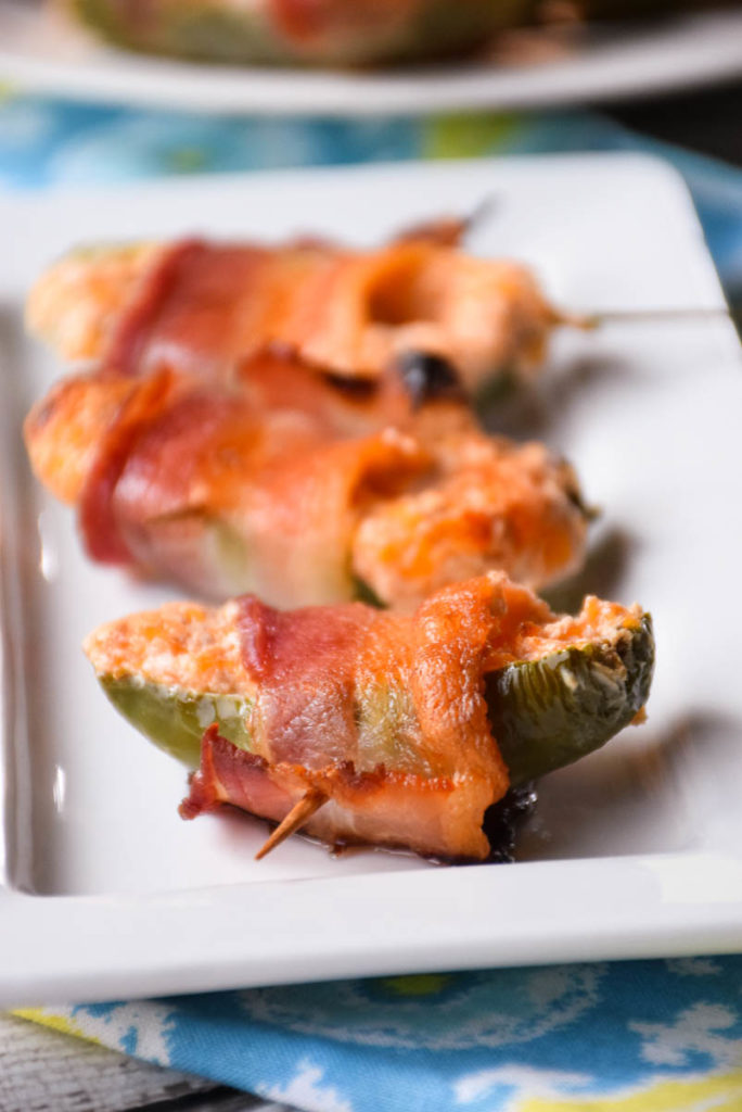 Sweet Bacon Wrapped Jalapeño Poppers are filled with cream cheese and cheddar cheese that has been blended with raspberry jam then wrapped in a blanket of salty bacon! This sweet heat treat will make crowds beg for more!