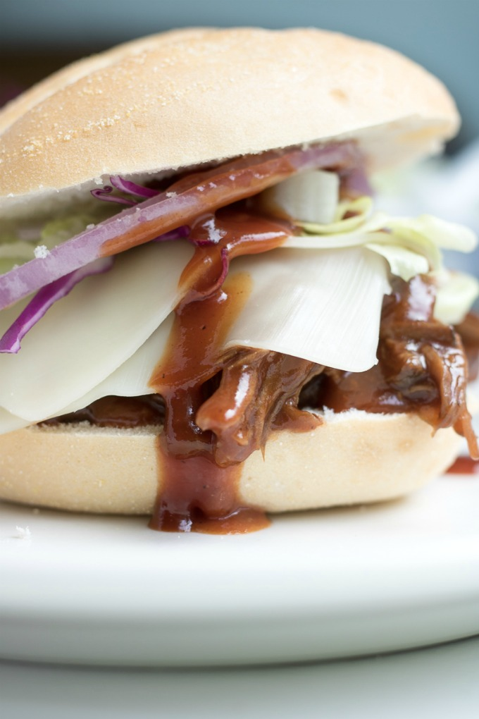 No one will be able to resist these Slow Cooker BBQ Slider Sandwiches! These savory BBQ Sliders are perfect for an easy dinner, potluck, or any gathering served with shaved lettuce, shaved crunchy red cabbage, red onion, and cheese.