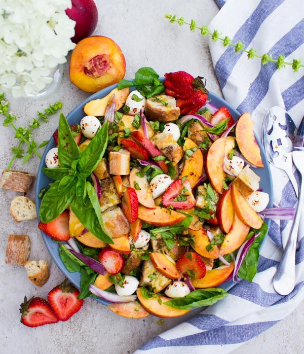 This Basil Peach Panzanella Salad is what farmers markets were made for! A tuscan salad with a twist, this simple, 20-minute recipe uses seasonal fruits and vegetables to create an international dish that's the perfect lunch, dinner side, or outdoor potluck.
