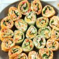 Colorful and delicious, Veggie Tortilla Pinwheels Appetizer is easy to make for tailgating. These small bites are the perfect healthy appetizer!