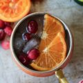 Looking for a refreshing holiday drink? Grab a copper mug and make this amazing Cranberry Orange Moscow Mule! Zesty, fresh, and delicious; this cocktail is exactly what your party needs.