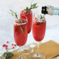 Everyone will love these Pomegranate Champagne Cocktails at your next winter get together! Made with homemade rosemary simple syrup, fresh pomegranate, and sparking pomegranate juice, these cocktails will help say cheers to whatever you're celebrating.