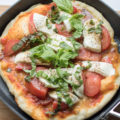 This Homemade Grilled Caprese Pizza is a vegetarian dish made from scratch. Topped with the fresh flavors of tomato, basil, and mozzarella on an easy homemade pizza crust, these single serve pizzas are perfect if you're cooking for two for date night.
