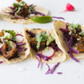Light and crispy, these Shrimp Tacos with red cabbage slaw and a homemade avocado cilantro sauce are a cheap healthy meal that's perfect for a weeknight dinner, summer entertaining, or a date night in.