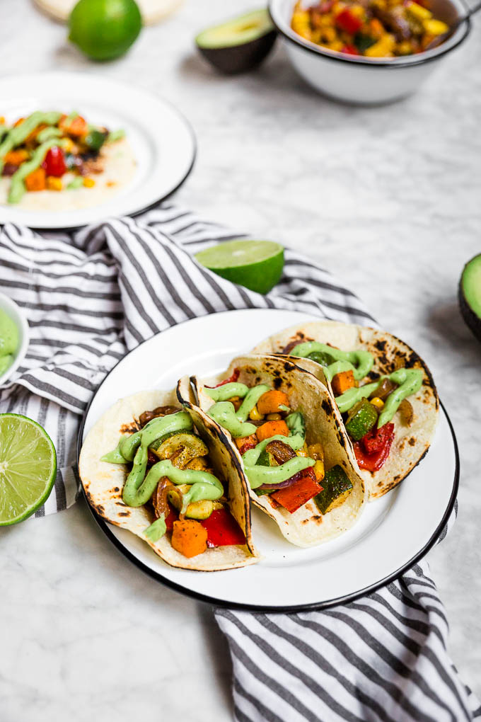Learn to make these Roasted Veggie Tacos with Avocado Crema like a pro to impress dinner guests. This cheap healthy meal is a vegetarian dinner full of vibrant colors and flavors.