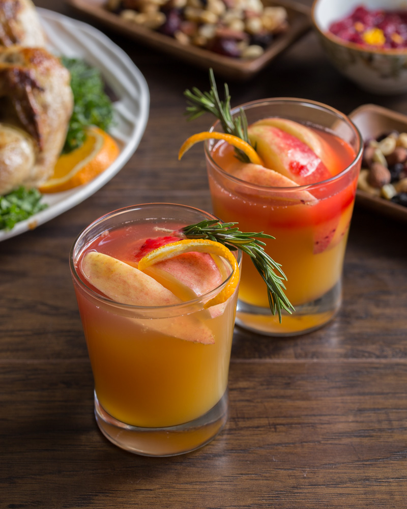Sweet, tart, and bubbly, this Cranberry Apple Cider Fizz is the perfect mocktail for your holiday menu. This festive drink embodies the fall flavors of apple, cranberry, orange, and rosemary. Booze it up for a fall cocktail you'll love!