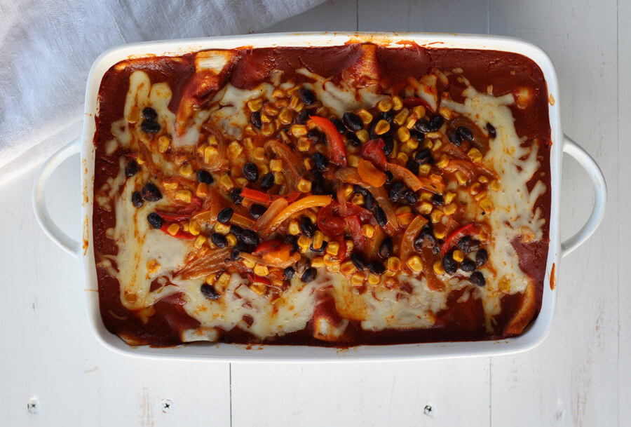 This lightened up version of Mexican-inspired enchiladas is big on flavor. Loaded with sweet peppers, onions, black beans, and corn, Veggie Lovers Vegetable Enchiladas are smothered in a delicious homemade enchilada sauce and melty cheese.