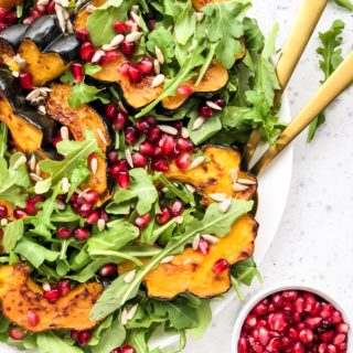 This Roasted Acorn Squash Salad is full of peppery arugula, sunflower seeds, pomegranate seeds, and topped with a simple homemade vinaigrette. A winter salad that's perfect for a weeknight dinner or healthy lunch.