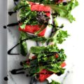 Impress your friends with this delectable, seasonal Balsamic Glazed Grilled Watermelon Stacked Salad recipe. The homemade balsamic glaze highlights the fresh flavors of the watermelon, arugula, and mozzarella.